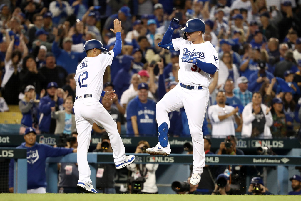 Joc Pederson #31 of the Los Angeles Dodgers celebrates with third base coach Dino Ebel #12 after his solo home run in the eighth inning of game one of the National League Division Series against the Washington Nationals to make it 6-0 at Dodger Stadium on October 03, 2019 in Los Angeles, California.