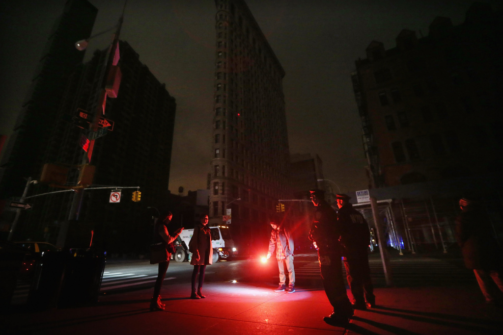 Police gather to tell a man to put out the road flare he found and was using as an impromptu flashlight while walking with friends in front of a darkened Flatiron Building in a section of Manhattan still in a blackout following Hurricane Sandy on October 30, 2012 in New York City. The storm has claimed at least 40 lives in the United States, and has caused massive flooding across much of the Atlantic seaboard. US President Barack Obama has declared the situation a 'major disaster' for large areas of the US East Coast including New York City.