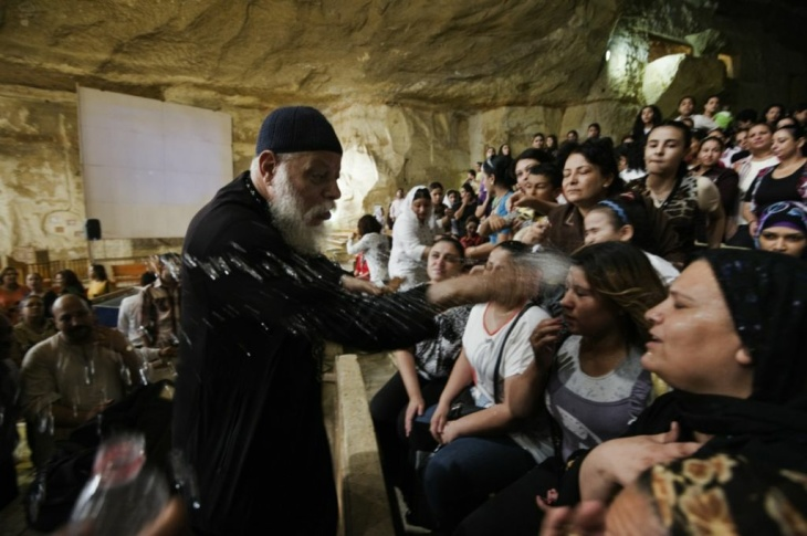 Worshippers attend a service as Coptic priest Father Samaan Ibrahim reads his sermon on July 26, 2012 at the St Samaans (Simon) Church also known as the Cave Church in the Mokattam village, nicknamed as