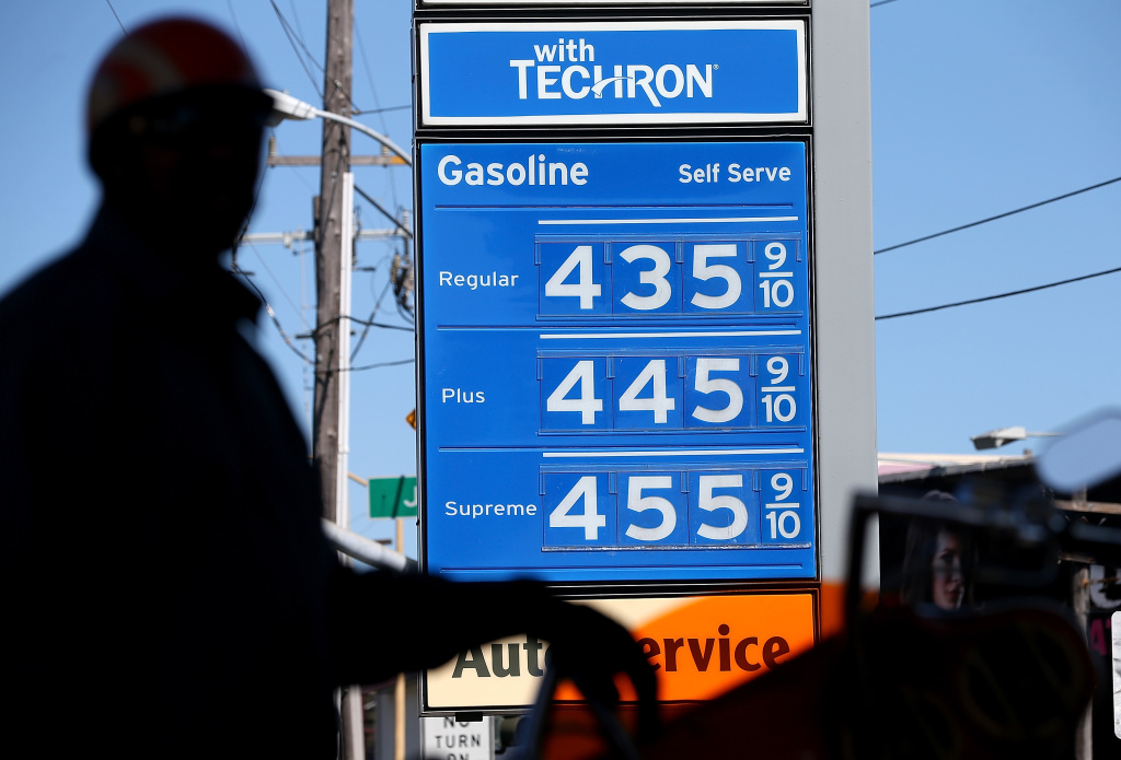 Gas prices are displayed as a motorcyclist pumps gas into his motorcycle at a Chevron gas station on March 1, 2013 in San Francisco, California.