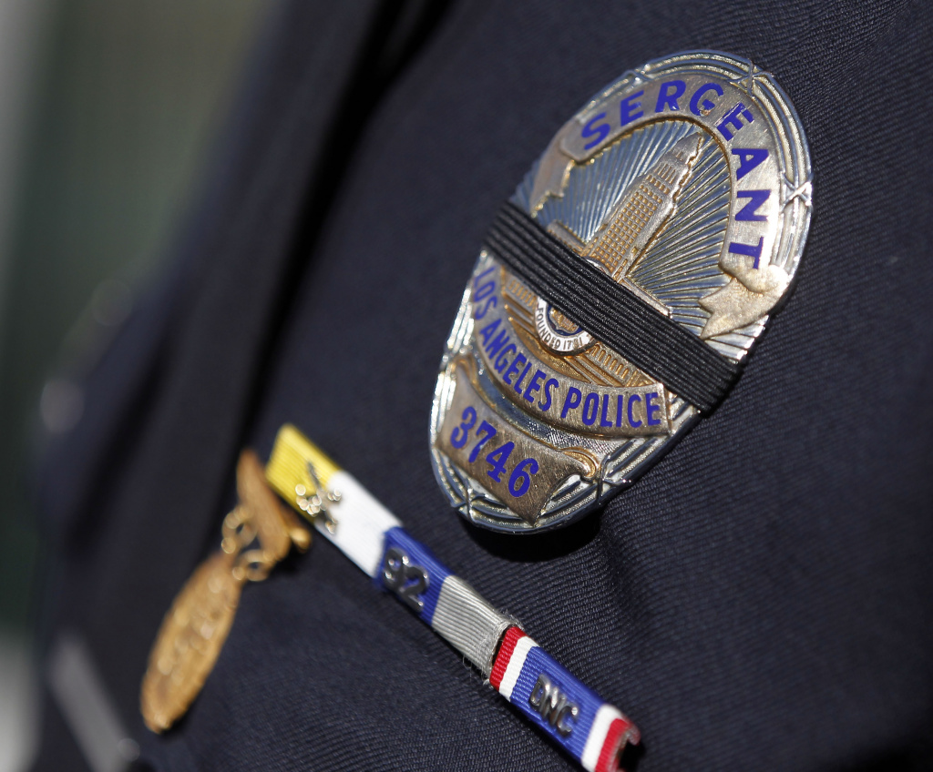 A file photo shows the badge of an LAPD officer covered with a black band, a practice that honors fallen officers. Last week, LAPD Officer Nicholas Lee was killed when his patrol car collided with a commercial truck in Beverly Hills.