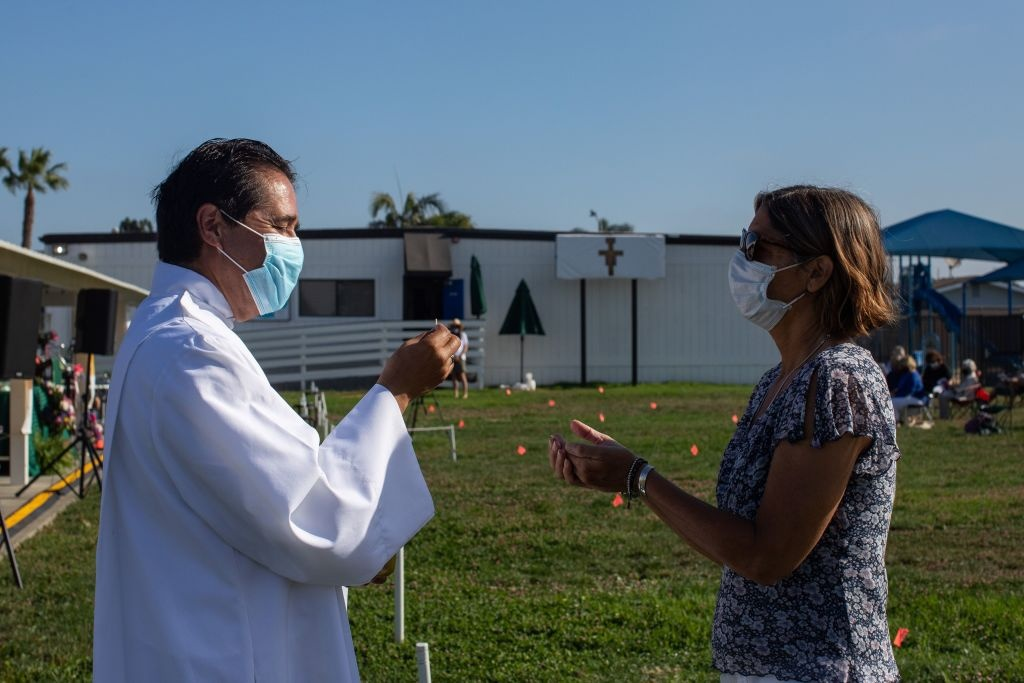 A priest wearing a facemask gives Communion to a woman at an outdoor Sunday service at Saints Simon & Jude Catholic Church in Huntington Beach, California, on July 19, 2020.