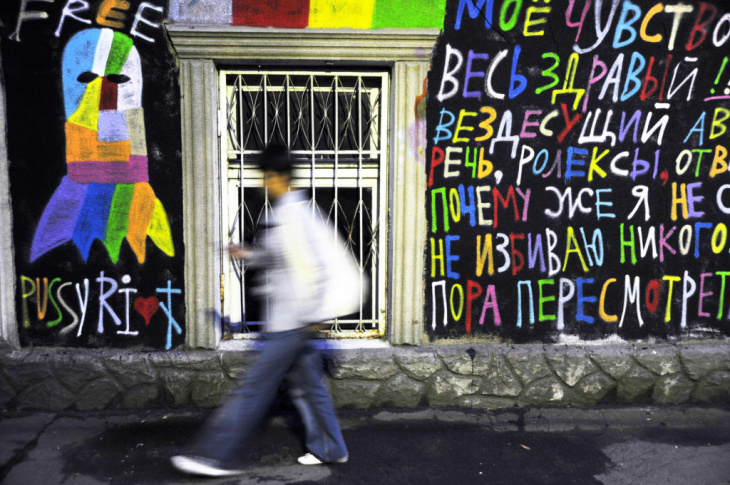 A man walks past a grafitti in support o
