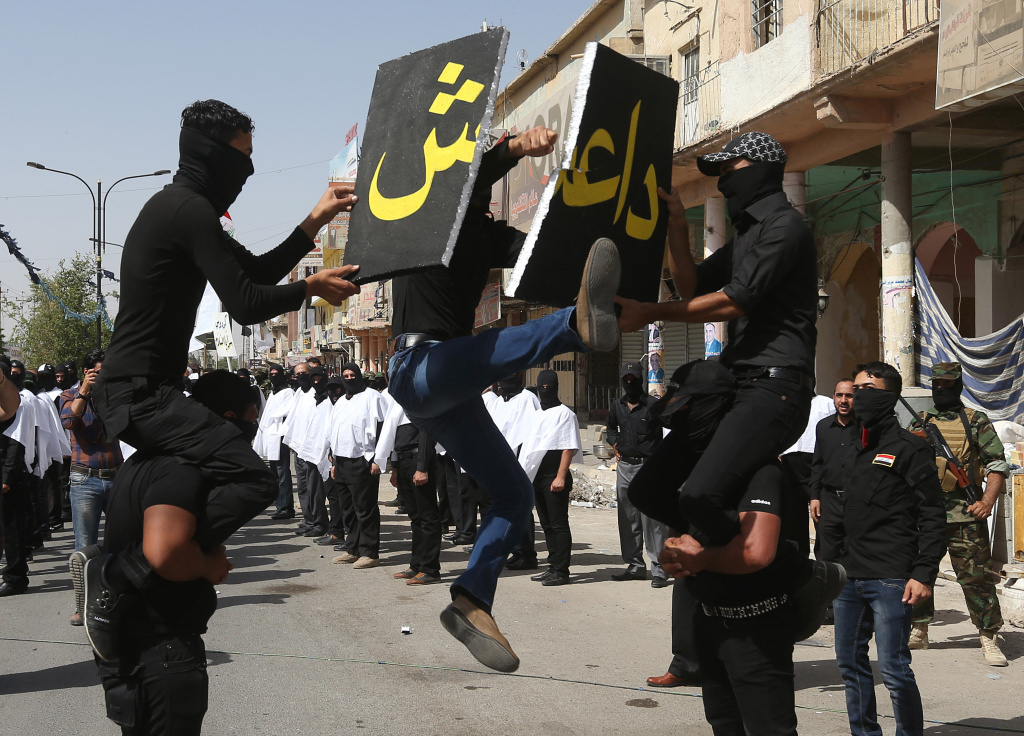 An Iraqi Shiite militiaman, a follower of Shiite cleric Muqtada al-Sadr, jumps to break a placard with the name of the self-proclaimed Islamic State of Iraq and Syria during a parade, in the northern oil rich province of Kirkuk, Iraq, on Saturday.