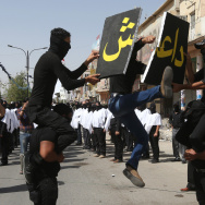 An Iraqi Shiite militiaman, a follower of Shiite cleric Muqtada al-Sadr, jumps to break a placard with the name of the Islamic State of Iraq and Syria (ISIS) during a parade, in the northern oil rich province of Kirkuk, Iraq, on Saturday.