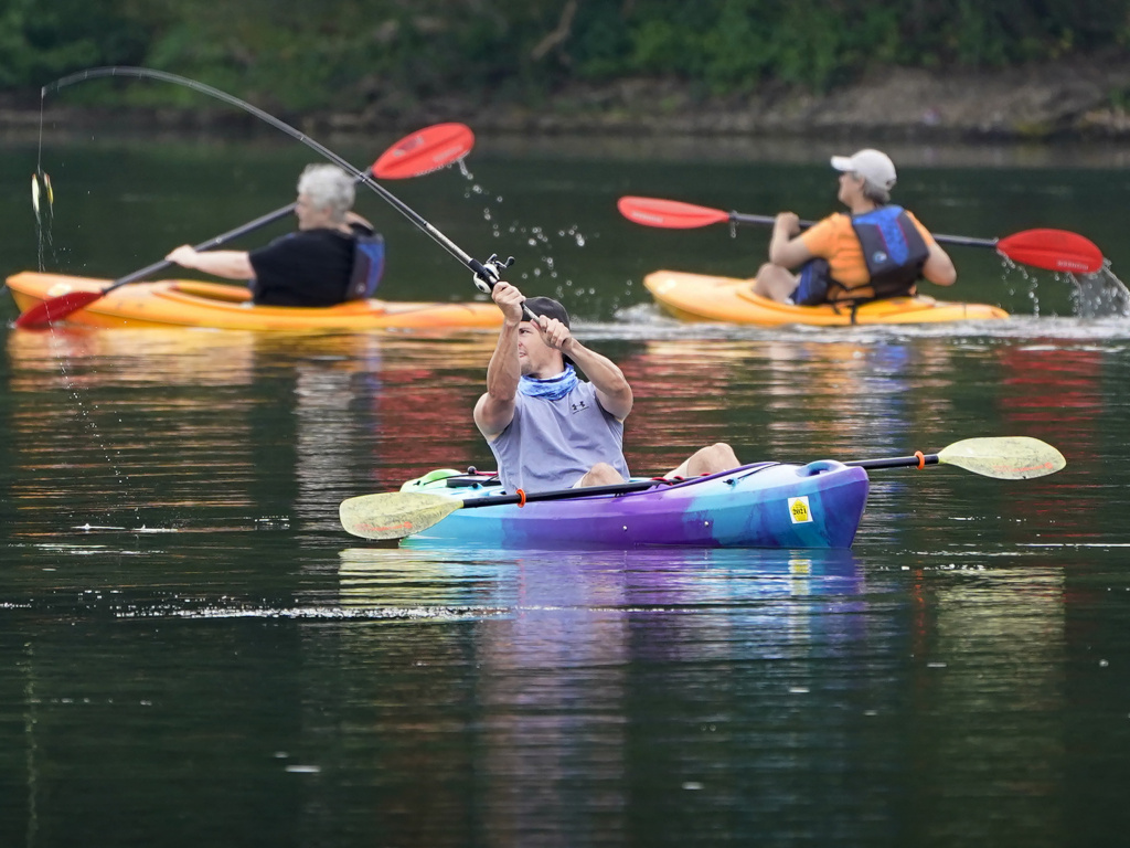 A fisherman in a kayak makes a cast on Lake Arthur at Moraine State Park in Portersville, Pa. Sales of camping, outdoor and recreational equipment have been surging.