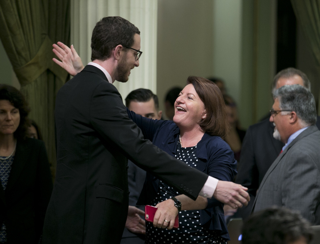 State Sen. Toni Atkins, D-San Diego, receives congratulations from Sen. Scott Wiener, D-San Francisco, after her housing measure was approved by the state Assembly, Thursday, Sept. 14, 2017, in Sacramento.