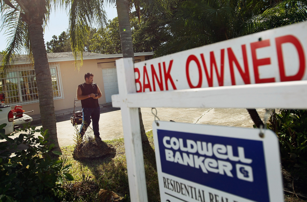 File: Renzo Salazar maintains the yard around a foreclosed home after the bank hired him to keep the home from falling into complete dilapidation on November 10, 2011 in Miami, Florida.