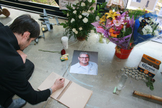 A visitor writes a message for Norman Schureman, a teacher at Art Center College of Design in Pasadena, who was shot on March 21, 2010.