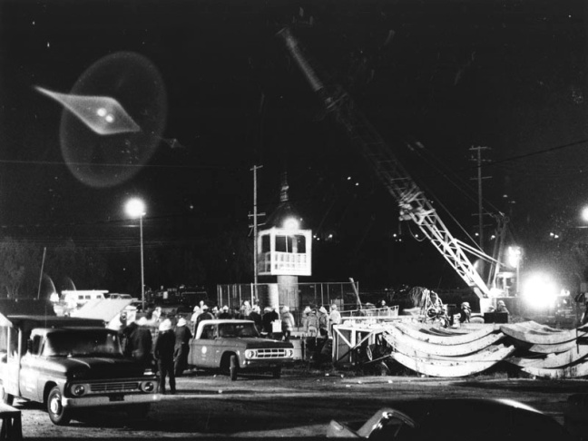 The brightly lit rescue scene at the entrance to the Sylmar water district tunnel is a harsh contrast against the dark night. Rescue workers desperately work against time, looking for possible survivors trapped inside the tunnel. Photograph dated June 25, 1971.