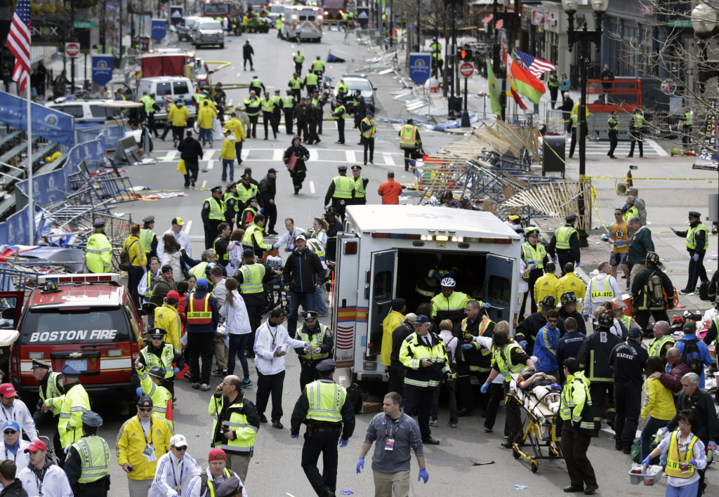 Medical workers aid injured people at the finish line of the 2013 Boston Marathon following an explosion in Boston, Monday, April 15, 2013.  Two explosions shattered the euphoria of the Boston Marathon finish line on Monday, sending authorities out on the course to carry off the injured while the stragglers were rerouted away from the smoking site of the blasts.