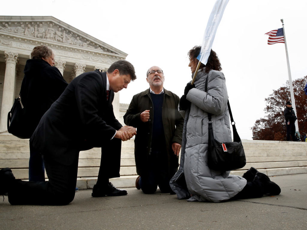 The Rev. Brad Wells, left, the Rev. Patrick Mahoney and Paula Oas, kneel in prayer in front of the Supreme Court, as the court hears the Masterpiece Cakeshop case.