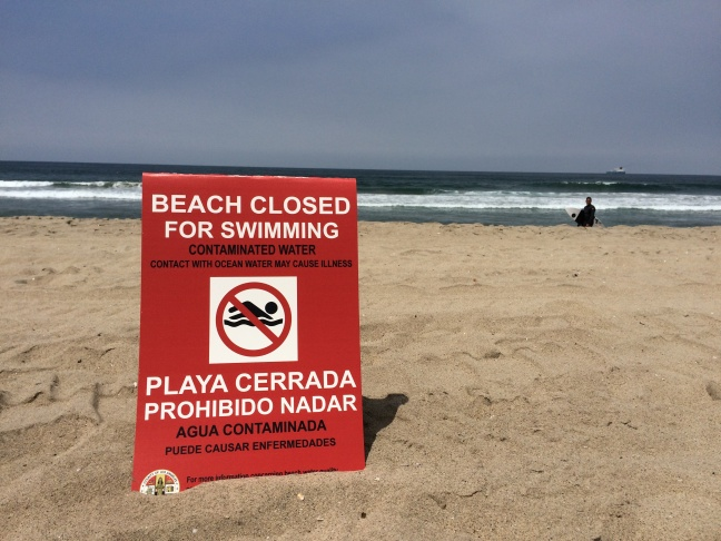 A sign posted at Manhattan Beach on Thursday, May 28, 2015, notifies the public of a closure after tar balls were discovered washed ashore Wednesday. Crews continued to work on cleanup efforts on Friday, though officials expected some affected beaches could be reopened later in the day.
