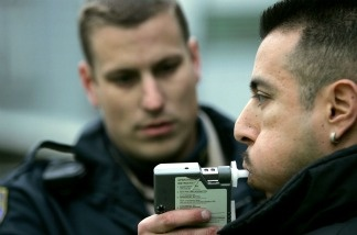 California Highway Patrol officer Mark Rossetti administers a breathalizer test to a man at a sobriety checkpoint.