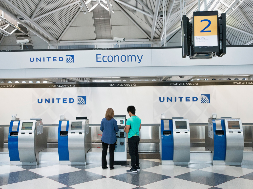 Passengers check in for flights with United Airlines at Chicago O'Hare International Airport. United, American and Delta now offer no-frills