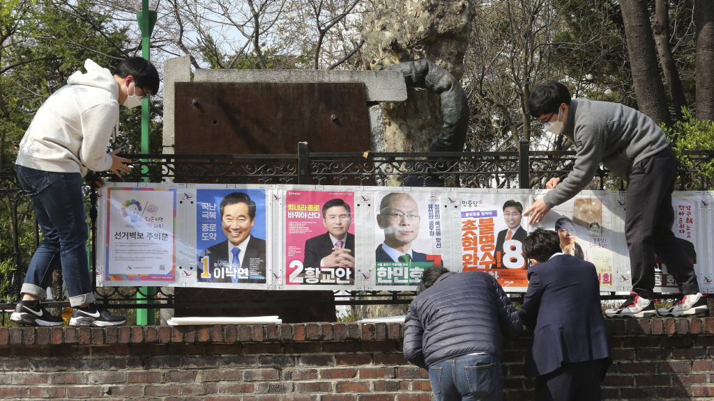 South Korean election officials put posters of candidates in Seoul, South Korea, on April 2. The country will hold April 15 legislative elections on schedule, and the government's handling of the coronavirus pandemic is a major issue in the vote.