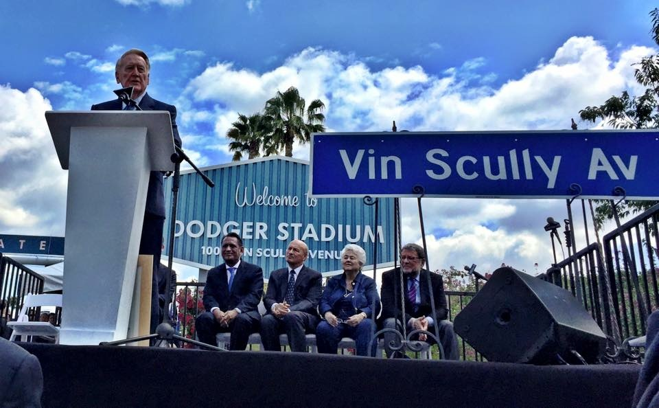 Vin Scully addresses the crowd outside Dodger Stadium, which now resides at 1000 Vin Scully Avenue. Seated are LA City Councilmember Gil Cedillo, who sponsored the renaming bill; Dodgers President Stan Kasten; former LA City Councilmember Roz Wyman, who brought the Dodgers to LA; and Dodgers broadcaster Charlie Steiner.