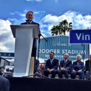 Vin Scully addresses the crowd at Dodger Stadium, which now resides at 1000 Vin Scully Avenue. Seated are LA City Councilmember Gil Cedillo, who sponsored the renaming bill; Dodgers President Stan Kasten; former LA City Councilmember Roz Wyman, who brought the Dodgers to LA; and Dodgers broadcaster Charlie Steiner.