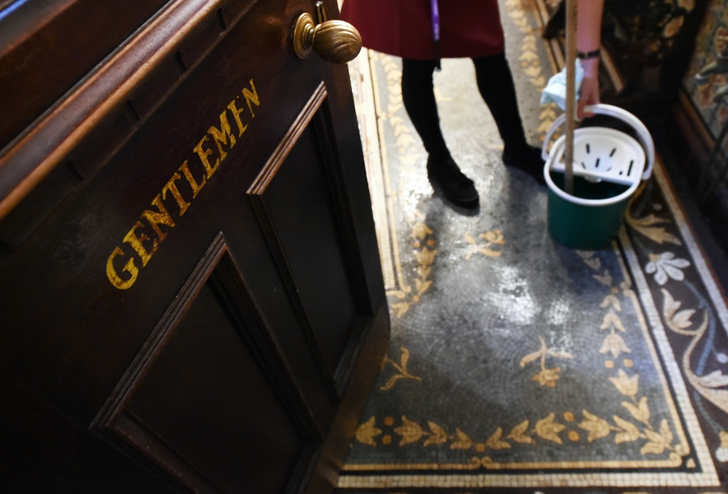A member of staff cleans the ornate men's toilets in the Philharmonic Dining Rooms in Liverpool, north west England on November 15, 2017.