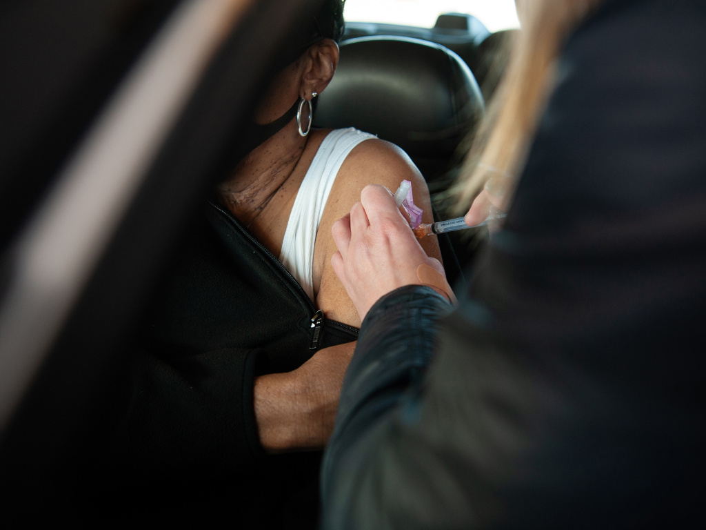 A health care worker at a drive-through site in Greenville, Miss., administers a COVID-19 vaccine shot in January. Mississippi was one of the first states to add a body mass index of 30 or more (a rough gauge of obesity) to its current list of qualifying medical conditions for vaccine eligibility.