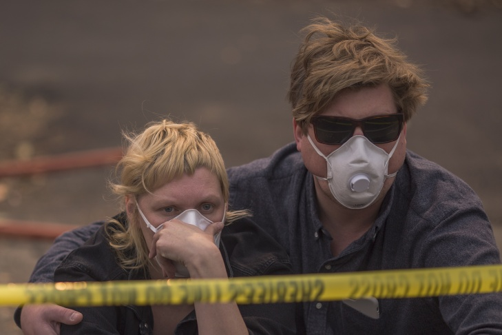 A couple waits in vain to be escorted to pick up possessions from their home inside an evacuation zone on October 11, 2017 in Napa, California. Escorts to were called for the rest of the day due to lack of available officers. In one of the worst wildfires in state history, at least 3,500 homes have burned and  at least 23 people were killed as more than 20 wildfires spread with little containment in eight Northern California counties.