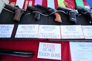 Handguns are displayed for sale at the Crossroads of the West Gun Show at the Pima County Fairgrounds on Jan. 15, 2011 in Tucson. Today marks one week since Jared Lee Loughner killed six and injured several others outside a grocery store in Tuscon.