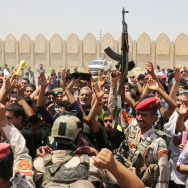 Iraqi Army soldiers and volunteers chant slogans against the al-Qaida inspired group Islamic State of Iraq and the Levant (ISIS), inside of the main army recruiting center in Baghdad on Saturday.