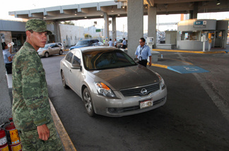 A Mexican soldier controls traffic at the Mexico-U.S. border customs post in Ciudad Juarez. Over the years, many undocumented immigrants from Mexico have been stuck in Juarez long-term after traveling there from the U.S. to apply for permission to return legally.