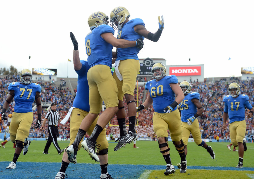 Joseph Fauria #8 of the UCLA Bruins celebrates his touchdown with Jerry Johnson #9 for a 17-0 lead over the USC Trojans at Rose Bowl on November 17, 2012 in Pasadena, California.
