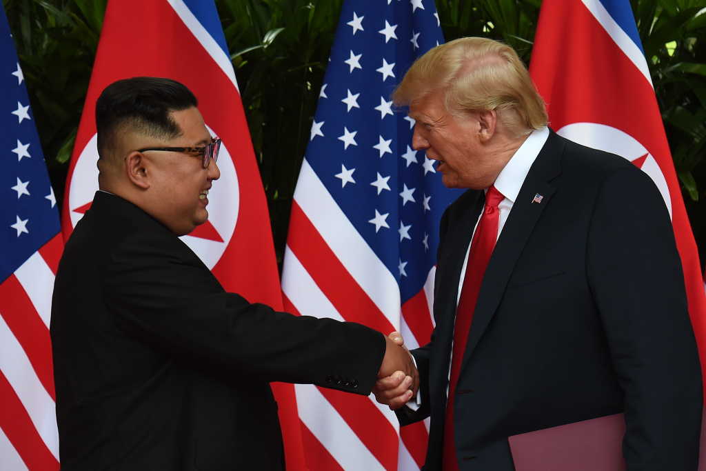 North Korea's leader Kim Jong Un (L) shakes hands with US President Donald Trump (R) after taking part in a signing ceremony at the end of their historic US-North Korea summit, at the Capella Hotel on Sentosa island in Singapore on June 12, 2018.