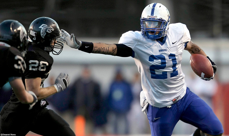 In Football We Trust's Harvey Langi (Right) stiff arms Alta's #28Parker Mirrison as Bingham and Alta play at Rice Eccles Stadium in the 5A semifinals as he honors his family during the game. Photo by Scott G Winterton Deseret News.