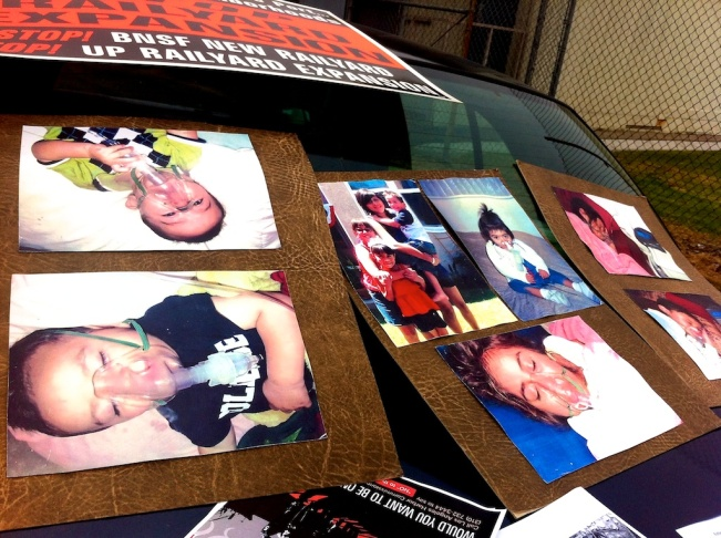 Outside Stephens Junior High School, concerned mothers, grandmothers and community residents display pictures of children with respiratory and other ailments they believe are connected to diesel pollution from locomotives.