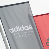 The logo of German sport brand Adidas is pictured on waving flags in front of the Adidas Headquarter in Herzogenaurach. An Adidas manager has been implicated in a bribery investigation involving recruitment efforts.