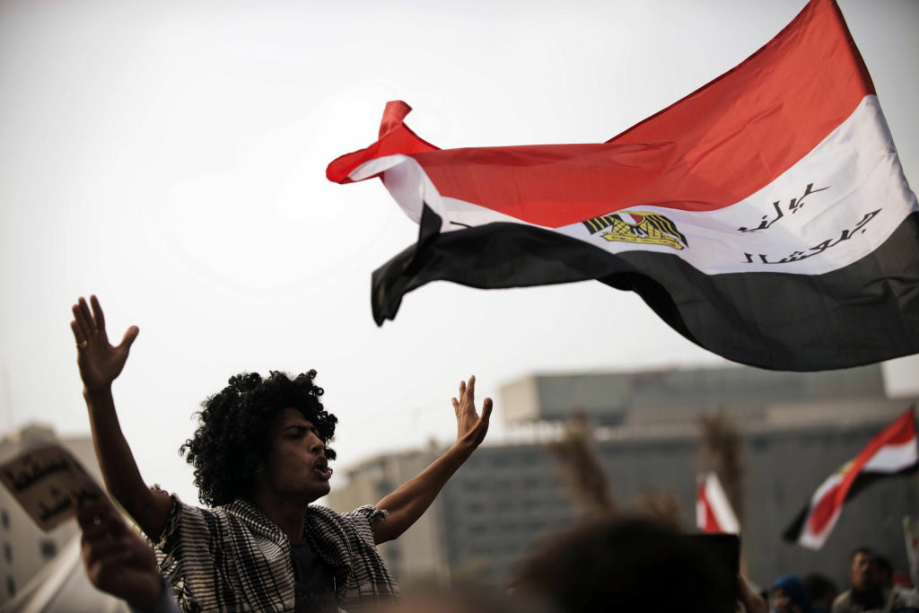Egyptian protesters wave their national flag as they shout political slogans against President Mohamed Morsi's decree granting himself broad powers during a demonstration in Cairo's Tahrir Square on November 27, 2012. The planned demonstrations come a day after Morsi met with the country's top judges in a bid to defuse the crisis over the decree, that has sparked deadly clashes and prompted judges and journalists to call for strike.