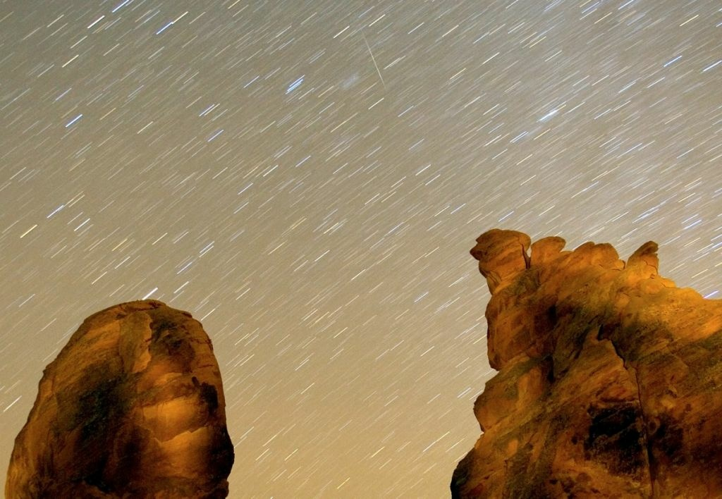 A Geminid meteor streaks diagonally across the sky against a field of star trails over one of the peaks of the Seven Sisters rock formation in this exposure early Dec. 14, 2007 in the Valley of Fire State Park in Nevada. The meteor display, known as the Geminid meteor shower because it appears to radiate from near the star Castor in the constellation Gemini, is thought to be the result of debris cast off from an asteroid-like object called 3200 Phaeton. The shower is visible every December.
