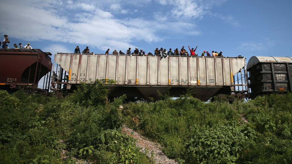 Migrants arrive at a rest stop in Ixtepec, Mexico, after a 15-hour ride atop a freight train headed north toward the U.S. border on Aug. 4, 2013. Thousands of migrants ride atop the trains, known as La Bestia, or The Beast, during their long and perilous journey through Mexico to the U.S.