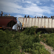 "Migrants arrive at a rest stop in Ixtepec, Mexico, after a 15-hour ride atop a freight train headed north toward the U.S. border on Aug. 4, 2013. Thousands of migrants ride atop the trains, known as ""La Bestia"" or The Beast, during their long and perilous journey through Mexico to the U.S. The Mexican government is now reportedly planning to increase railway surveillance as a way of deterring Central American migration north."