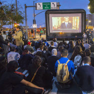 Onlookers watch as President Obama is shown on a projector near the intersection of Alameda St. and the 101 freeway in downtown Los Angeles on Thursday, Nov. 20 as he announced plans for executive action on immigration. GOP lawmakers unhappy with the immigration plan hope to counter it as part of the current federal budget battle.