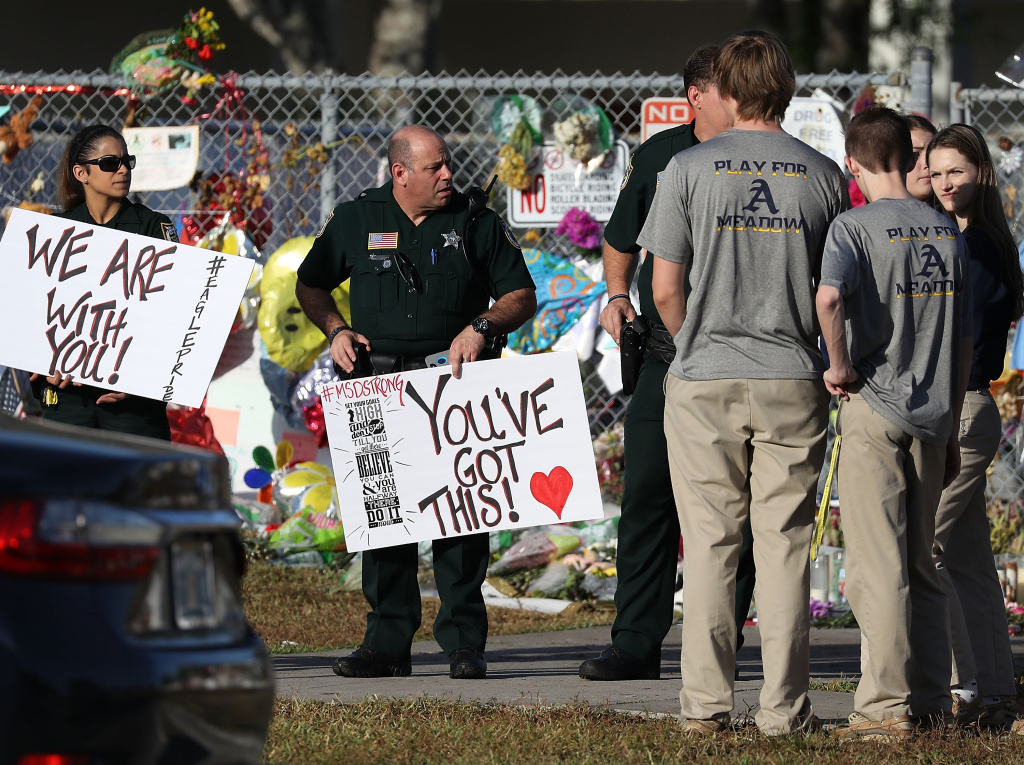 Broward County Sheriff officers welcome students as they arrive at Marjory Stoneman Douglas High School as students arrive to attend classes for the first time since the shooting that killed 17 people on February 14  at the school on February 28, 2018 in Parkland, Florida.