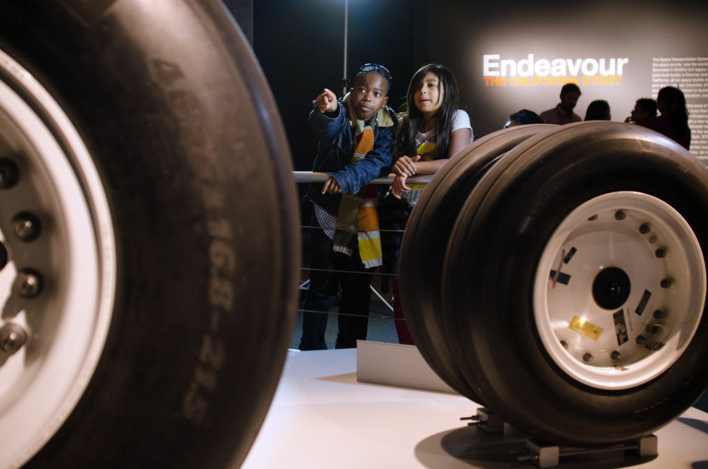 Two children look at the tires from STS-134, space shuttle Endeavour's last mission, during a preview of Endeavour: The California Story exhibition at the California Science Center.