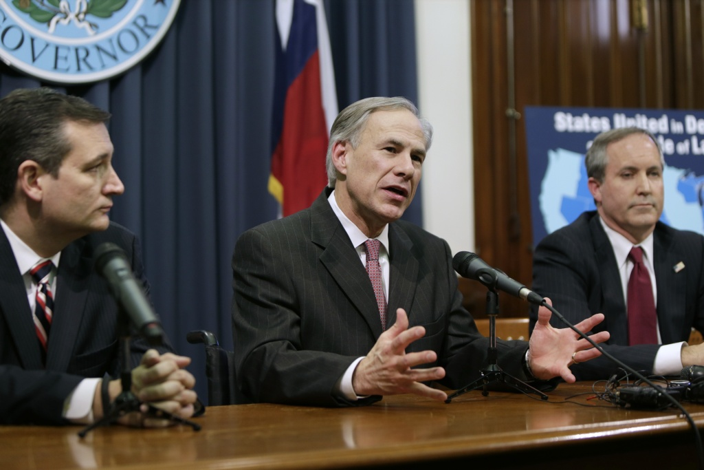 Governor Greg Abbott (C) speaks alongside U.S. Sen. Ted Cruz (R-TX) (L), Attorney General Ken Paxton (R) at a joint press conference February 18, 2015 in Austin, Texas.