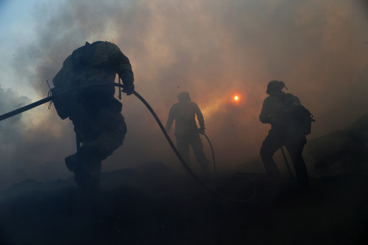 SYLMAR, CALIFORNIA - OCTOBER 12: Firefighters work on containing a flare up at a mulch supplier during the Saddleridge Fire on October 12, 2019 in Sylmar, California. The wind-driven fire has burned 7,500 acres and destroyed 76 structures, leaving one dead. (Photo by Mario Tama/Getty Images)