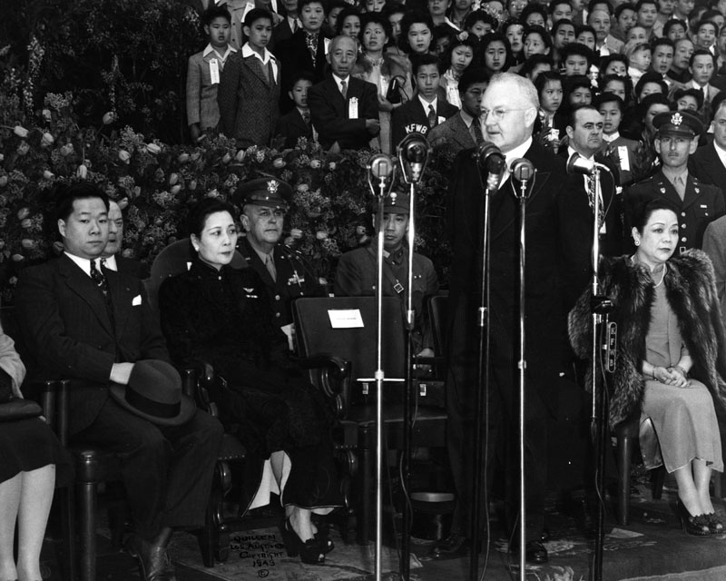LA Mayor Fletcher Bowron welcoming Madame Chiang Kai-Shek on her visit to Los Angeles on March 31, 1943. Madame Chiang Kai-Shek (seated left, center) was raising funds for China during World War II. Mrs. Bowron is seated behind him. His talk is being broadcast on various radio stations.