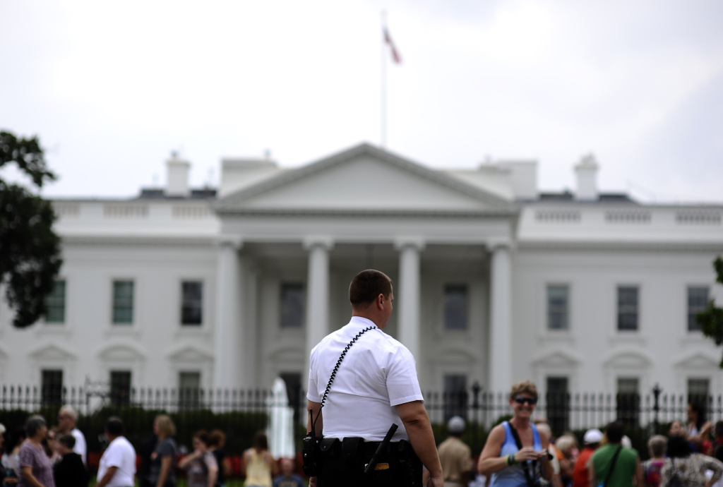 A member of US Secret Service uniform division keeps watch as tourists walk in front of the White House in Washington, DC.