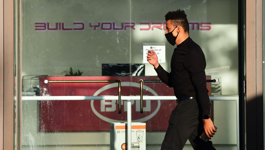 A man wearing a facemask walks past the BYD office in Los Angeles, California on May 13, 2020.
