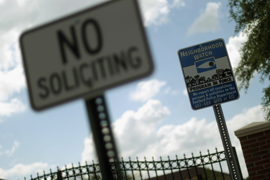 A neighborhood watch sign is seen in front of The Retreat at Twin Lakes gated community in Sanford, Florida.