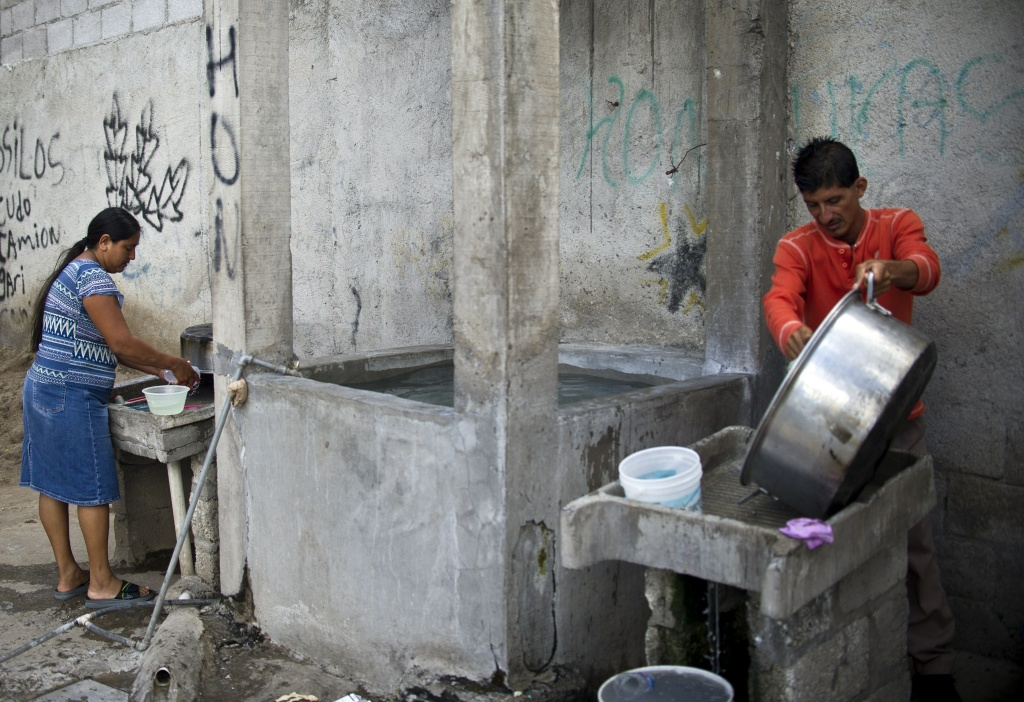 Central American migrants clean pots and dishes at the Sagrada Familia shelter as they wait for the so-called La Bestia (The Beast) cargo train, in an attempt to reach the US border, in Apizaco, Tlaxcala state, Mexico on July 22, 2014.