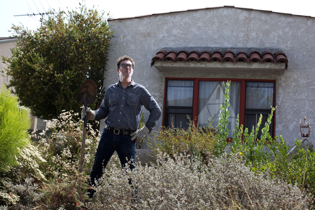 Tom Underhill stands in his front yard filled with California native plants at his home in Long Beach. Six years ago he replaced the lawn and flowers with draught-tolerant native plants. Underhill and his wife inadvertently received a property tax break of $250 for not using their share of municipal water, he said.