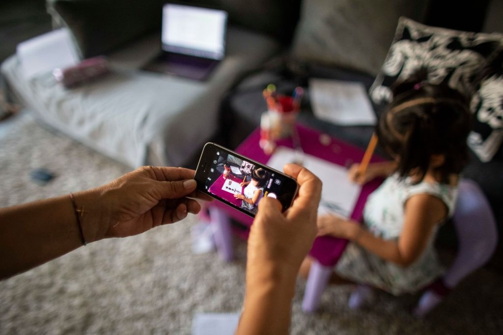 A mother takes a photo on her phone of  her daughter Kindergarten student while doing homework and then send it online to the teacher during the second month of quarantine in the Country on April 23, 2020 in Caracas, Venezuela.