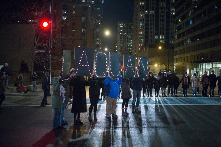 In this Tuesday, Nov. 24, 2015, file photo, a protester holds a sign as people rally for 17-year-old Laquan McDonald, who was shot 16 times by Chicago Police Department Officer Jason Van Dyke in Chicago.